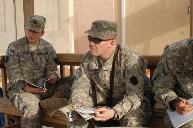 CAMP TAJI, Iraq - Spc. Lesley Schneider (at left) and Sgt. Philip Amos, both of Erie, Pa., with Headquarters and Headquarters Company, 1st Battalion, 112th Infantry, 56th Stryker Brigade Combat Team, trade hunting stories and read copies of Ducks Unlimited magazine, June 13, while waiting for the start of a cookout.