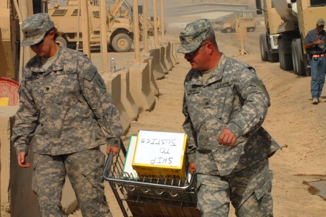 "BAGHDAD - Spc. Angelica Windley (left), a supply specialist from Washington, N.C., and Sgt. William Knapp, a logistics noncommissioned officer from Richmond, Va., both of Headquarters and Headquarters Company, 299th Brigade Support Battalion, 2nd Brigade, 1st Infantry Division, load supplies  before patrol rehearsal drills at Camp Liberty, June 22.  ""Our job is to make sure Soldiers have adequate supplies to be self-sufficient at the FOBs,"" said Knapp."