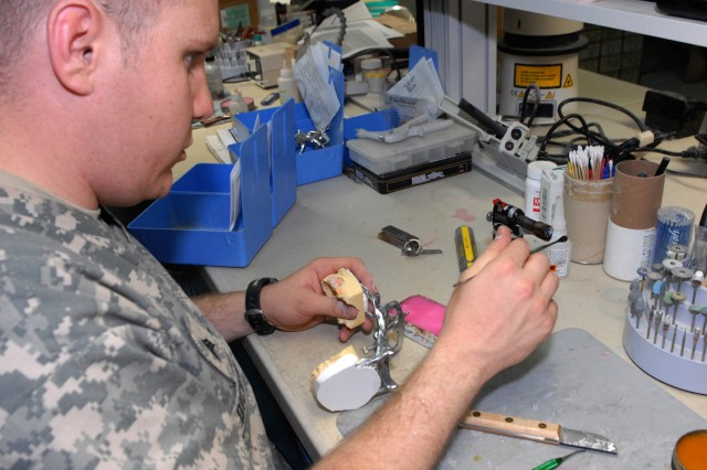"""BAGHDAD - Sgt. David Dickinson, who hails from Salt Lake City, assigned to the 464th Medical Company (DS), 421st Multifunctional Medical Battalion, 44th Medical Command, Multi-National Division-Baghdad, heats up a tool that gathers and molds wax to hold in a partial denture, June 24 at Camp Liberty. """"Stay away from sugar, tobacco, and brush at least once a day,"""" said Dickinson, a dental lab technician. """"We even supply toothbrushes, floss sticks, and dental floss for free."""""""