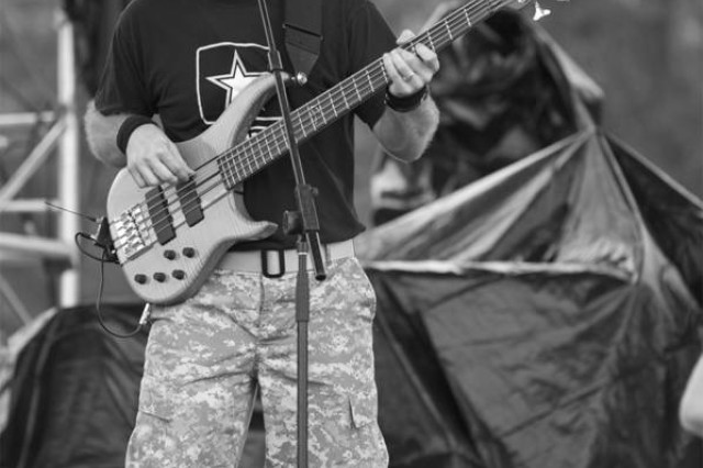 Sgt. 1st Class Pete Krasulski, bassist for The Volunteers, performs at Country USA in Oshkosh, Wis. More than 150 thousand festival-goers attended the Nation's premier country music festival.