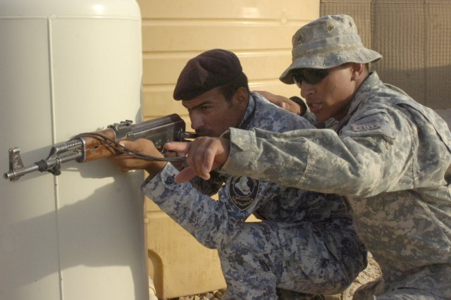 Staff Sgt. Damian Remijio, instructs a National Police officer assigned to the 3rd NP Brigade, 1st NP Division to keep his sights on a door during a training event, June 24, at Forward Operating Base Hammer, Iraq, located outside of eastern Baghdad.