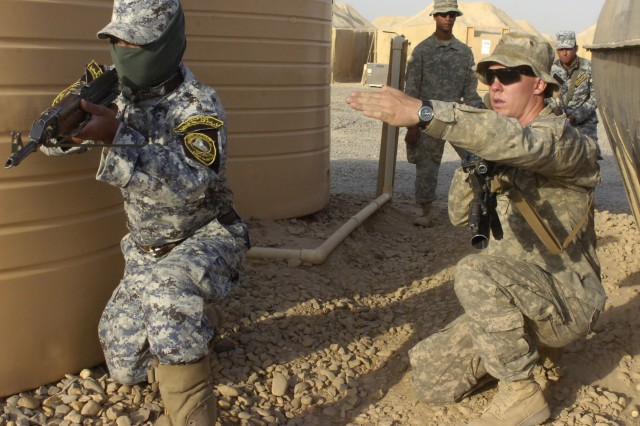Pvt. Nicholas Culpepper, of Raleigh, N.C., advises a National Police officer assigned to the 3rd NP Brigade, 1st NP Division to point his weapon toward a certain direction in order to provide security for his fellow officers who are entering and clearing a home during a training event, June 24, at Forward Operating Base Hammer, Iraq, located outside of eastern Baghdad. Culpepper and Paratroopers assigned to Troop K, 5th Squadron, 73rd Cavalry, 82nd Airborne Division, are training and mentoring their Iraqi partners as part of a two-week course in the unit's newly developed training academy.