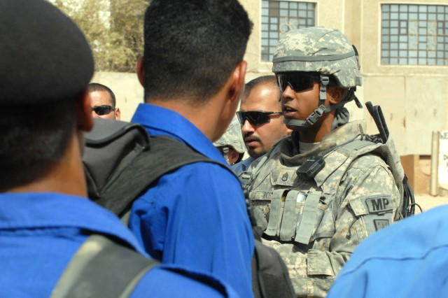 BAGHDAD - Staff Sgt. Maurice Rice (right), a squad leader from Chicago, assigned to the 463rd Military Police Company, 93rd Military Police Battalion, 8th Military Police Brigade, speaks with the Iraqi police of al-Mansour about maintaining police standards, June 24.