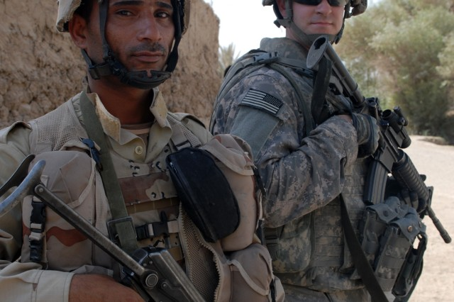 BAGHDAD - Spc. Jon Morris of Lakewood, Ohio, a medic assigned to Company A, 1st Combined Arms Battalion, 63rd Armored Regiment, 2nd Brigade Combat Team, 1st Infantry Division, stands with an Iraqi soldier during a joint combat patrol of al-Fallujean in the Abu Ghraib area here, June 24. The Co. A Soldiers and Iraqi soldiers of 1st Company, 4th Battalion, 24th Brigade, 6th Iraqi Army Division walked through the village, meeting with locals and discussing security concerns.