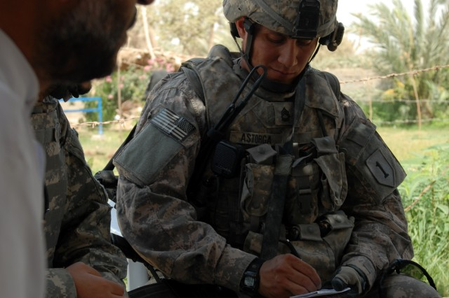 "BAGHDAD - Sgt. 1st Class Sesilio Astorga, a platoon sergeant assigned to Company A, 1st Combined Arms Battalion, 63rd Armored Regiment, 2nd Brigade Combat Team, 1st Infantry Division, takes down notes while discussing security and infrastructure concerns with Ali Matar Hussein in the village of al-Fallujean in the Abu Ghraib area here, June 24. Astorga, a native of Rexburg, Idaho, said he gained valuable insight in his first meeting with Hussein. ""It was good meeting him [Ali Matar Hussein] because of the hospitality he showed,"" Astorga said. ""He voiced his opinion and let me know the people are able to work with us and the Iraqi Army."""