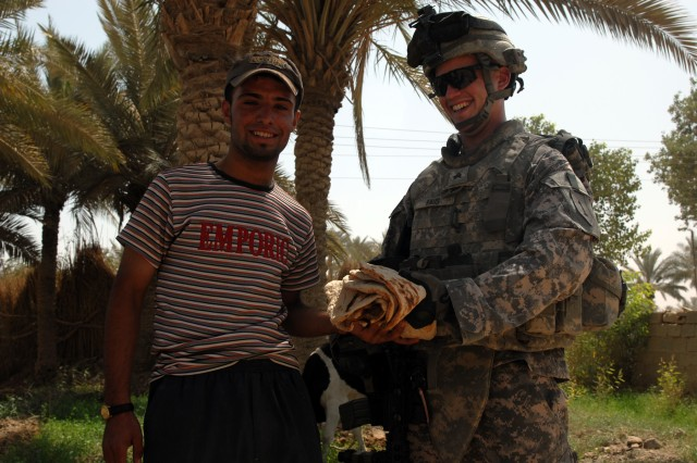 """BAGHDAD - Sgt. Brandt Faus accepts homemade bread from an Iraqi man in the village of al-Fallujean in the Abu Ghraib area here, June 24. Faus, an infantryman assigned to Company A, 1st Combined Arms Battalion, 63rd Armored Regiment, 2nd Brigade Combat Team, 1st Infantry Division, said the interaction with Iraqi citizens is a highlight of dismounted patrols. """"It feels good when they like you,"""" said Faus, a Phoenix native. """"It's cool when you see them smile at you."""" The Soldiers of Company A walked through Al-Fallujean on a joint combat patrol with the 1st Company, 4th Battalion, 24th Brigade, 6th Iraqi Army Division."""