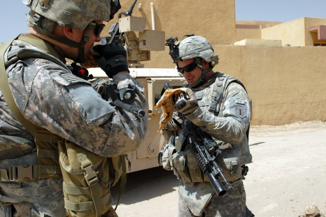 BAGHDAD - Staff Sgt. Ramon Esparaza-Reyes (left) of Yuma, Ariz., and Spc. Michael Thornton of Dallas share a piece of bread given to them by an Iraqi man in the village of al-Fallujean in the Abu Ghraib area here, June 24. Both Soldiers are infantrymen assigned to Company A, 1st Combined Arms Battalion, 63rd Armored Regiment, 2nd Brigade Combat Team, 1st Infantry Division. The Soldiers were on a joint combat patrol with Iraqi soldiers of 1st Company, 4th Battalion, 24th Brigade, 6th Iraqi Army Division.