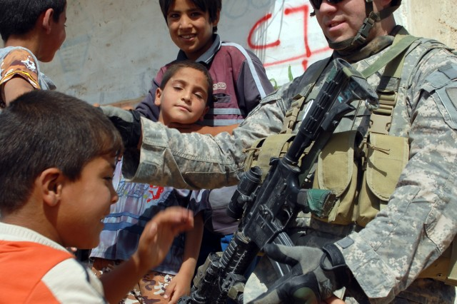 BAGHDAD - Staff Sgt. Ramon Esparaza-Reyes of Yuma, Ariz. greets Iraqi children during a patrol of the village of al-Fallujean in the Abu Ghraib area here, June 24. Esparaza is an infantryman assigned to Company A, 1st Combined Arms Battalion, 63rd Armored Regiment, 2nd Brigade Combat Team, 1st Infantry Division.