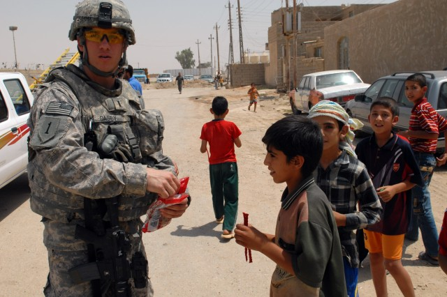 BAGHDAD - 1st Lt. Justin Casey, from Ogdensburg, N.Y., assigned to the Joint Projects Management Office, 2nd Brigade, 1st Infantry Division, hands out candy to Iraqi children in the Nasir Wa Salam neighborhood here, June 25. Children seemed to come from every direction when Casey pulled out a bag of candy, all clamoring for a piece.