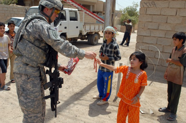 BAGHDAD - 1st Lt. Justin Casey, an Ogdensburg, N.Y. native, assigned to the Joint Projects Management Office, 2nd Brigade, 1st Infantry Division, gives candy to an Iraqi girl in the Nasir Wa Salam neighborhood here, June 25. While out on missions, Casey said, he always tries to bring some candy with him to hand out to the children.