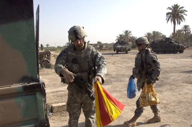 """BAGHDAD - Staff Sgt. Joel Oravitz from Beaver Falls, Pa., and Spc. Mark Laird from Phoenix, Ariz., both of the 2nd Battalion, 112th Infantry Regiment, """"Paxton Rangers"""", 2nd Heavy Brigade Combat Team, 1st Infantry Division, Multi-National Division-Baghdad load bags of food onto an Iraqi Army truck. The food was distributed to residents of the """"1st of June"""" area of Abu Ghraib during a joint foot patrol on June 25. The joint patrols are designed to improve the relationships between the Iraqi Army and the residents of the areas they secure."""