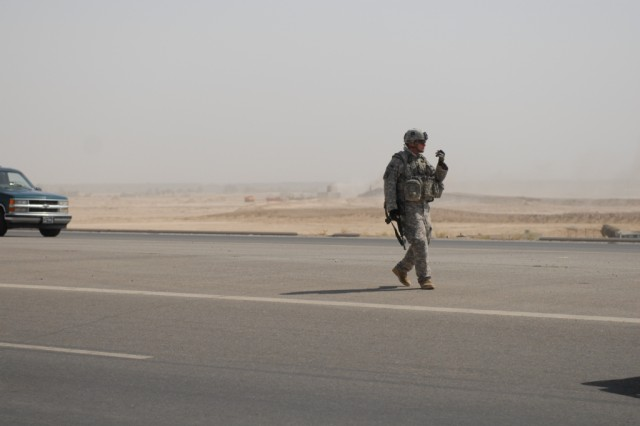 FALLUJAH, Iraq – Staff Sgt. Theodore Montgomery, a squad leader in B Company, 2nd Battalion 142nd Infantry, 56th Infantry Brigade Combat Team, directs traffic during recovery operations after a vehicle breakdown on the outskirts of Fallujah, June 24. Montgomery, serving in his second tour to Iraq, has been on the road executing the convoy escort mission to a tune of more than 20,000 miles in only seven months.