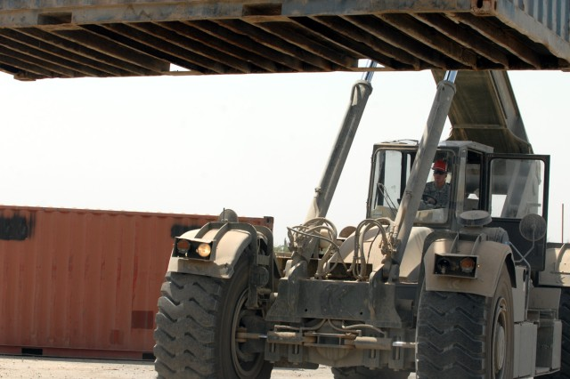BAGHDAD - Sgt. Darrel Whitton, a Gouverner, N.Y. native, and automotive logistics Soldier assigned to Company A, 299th Brigade Support Battalion, 2nd Brigade, 1st Infantry Division, moves a conex with a Rough Terrain Container Handler (RTCH) at Camp Liberty, June 26.  The RTCH is used to move large containers.