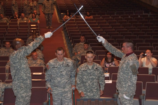 FORT CARSON, Colo.-Sgt. 1st Class Justin Widhalm, second from left, walks with Sgt. Gavin Sibayan as he crosses the line of authority during the Warrior Transition Battalion's first noncommissioned officer induction ceremony June 24 at McMahon Auditorium here.