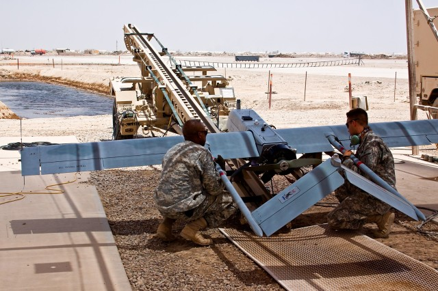 TAJI, Iraq - Prepping for a launch, Sgt. Donald Melvin (left), an unmanned aerial vehicle mechanic, from Columbus, Miss., a 1st Infantry Division Soldier attached to 2nd Battalion, 1st Air Cavalry Brigade, 1st Cavalry Division, Multi-National Division - Baghdad, and Spc. Stephen Cantrell (right), from Wichita Falls, Texas, a UAV mechanic, in 1st Inf. Div., also attached to the 1st ACB, set a UAV onto a ramp that will help propel the aircraft into flight at Camp Taji, Iraq, north of Baghdad, June 25.