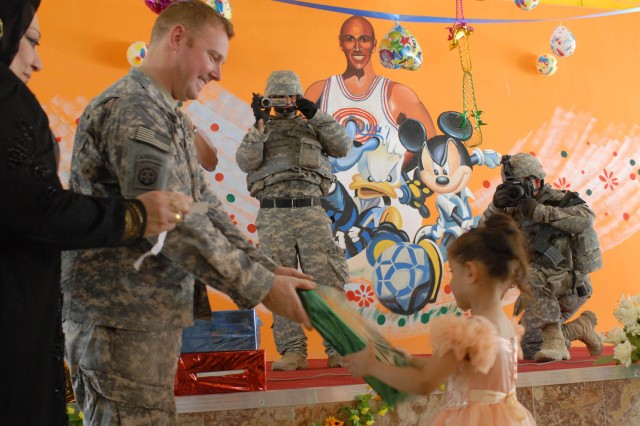 BAGHDAD - Waltham, Mass. native, Capt. William Murphy, team leader for the Civil Affairs Team attached to 1st Battalion, 5th Cavalry Regiment, attached to the 1st Brigade Combat Team, 1st Cavalry Division hands a little girl, who attends the Al Areej Kindergarten, a present after the renovation completed celebration held at the school in Adhamiyah June 25.