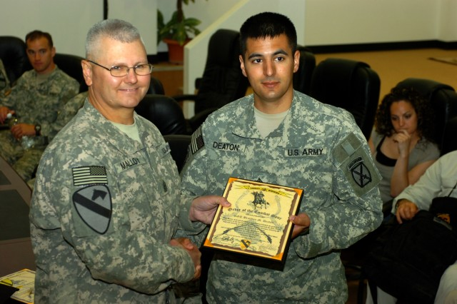BAGHDAD - Command Sgt. Maj. Rory Malloy (left), senior enlisted advisor, 1st Cavalry Division and Multi-National Division-Baghdad, presents the Order of the Combat Spur to Topsham, Maine native, Sgt. Brandon Deaton, an infantryman with the 2nd Brigade Combat Team, 10th Mountain Division, during a visit by Operation Proper Exit Soldiers to Camp Liberty, Iraq June 27. Operation Proper Exit allows wounded warriors the opportunity to find closure and to see recent security gains in Iraq, many of which are the direct result of their sacrifices.