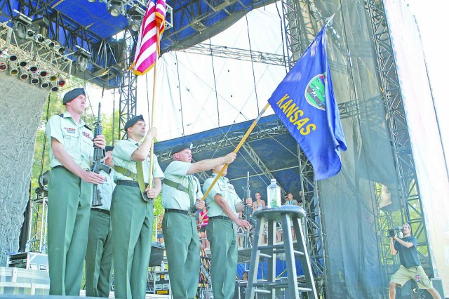 A color guard from the Combat Aviation Brigade, 1st Inf. Div., stands on stage during the singing of the national anthem before Kellie Pickler's performance June 28 at Tuttle Creek State Park in Manhattan for Country Stampede.