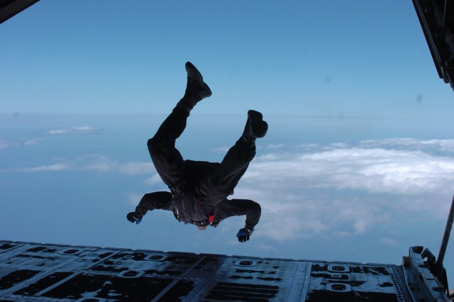 Chief Petty Officer Nathaniel Spencer, air operations leader for the Navy's explosive ordnance disposal team Mobile Unit 8, performs a high altitude jump from the rear tailgate of a C-130 Hercules at Naval Air Station Sigonella June 23 in Sicily, Italy.
