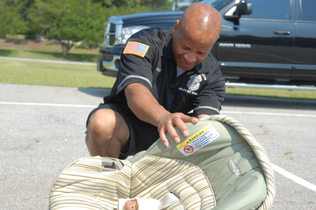 Officer Lionel Brown, a DA police officer, inspects a child safety seat as part of a certification process last week. Brown was certified to inspect the seats and teach others how to correctly install them.