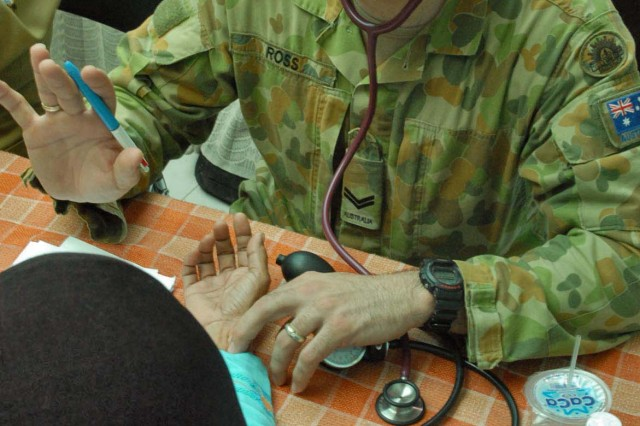 Australian Cpl. Jason Ross, medic, checks the blood pressure of a woman in Ciburuy Villiage, near Bandung, Indonesia, June 29 as part of the Medical Readiness Exercise Tendon Valiant. Doctors and medics from 12 countries provided medical care to nine sites in the Bandung area. Tendon Valiant is an annual, multi-national, Medical Readiness Exercise to improve security operation and medical interoperability between the nations.