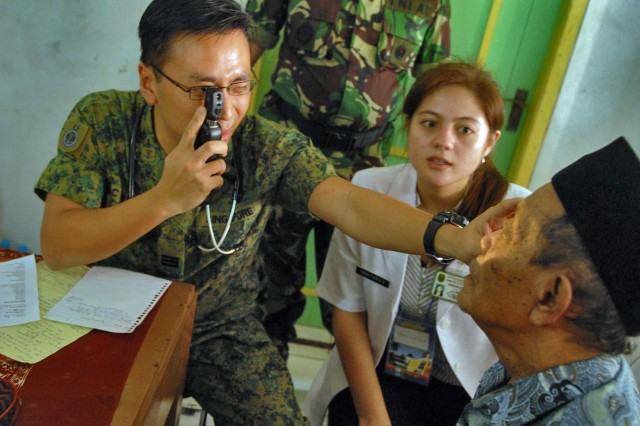 A doctor from Singapore, checks the eyes of a patient in Ciburuy Villiage, near Bandung, Indonesia, June 29 as part of the Medical Readiness Exercise Tendon Valiant.  Doctors and medics from 12 countries provided medical care to nine sites in the Bandung area. Tendon Valiant is an annual, multi-national, Medical Readiness Exercise to improve security operation and medical interoperability between the nations. During the five-day exercise, the doctors and medics treated more than 2,000 patients.