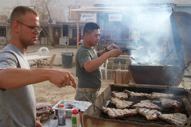 Staff Sgt. Jeffrey Brown, a Greenwood, Ind. native and Staff Sgt. Tien Do, a native of Indianapolis, both with the 1538th Trans. Co., supervises the barbecue grills during the 1538th Trans. Co., 419th Combat Sustainment Support Battalion, 10th Sustainment Brigade's farewell celebration at Camp Taji, Iraq.