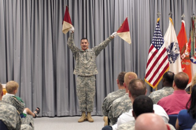 Sgt. 1st Class Ronald Eckert, 93rd Signal Brigade, demonstrates the Semaphore/Wigwag flag signaling system during the 149th Annual  Army Signal Corps Anniversary celebration June 24 at the Transportation Museum. The event also featured remarks by Col. James Garrison, 93rd Signal Bde. commander, a slideshow, a performance of the Signal Corps song by Spc. Tina McCoy, and a recounting of the Signal Corps history.