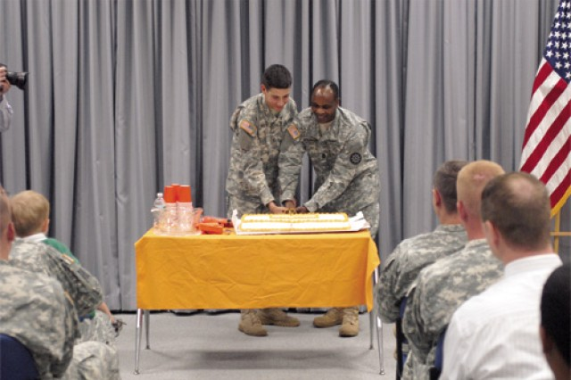 Command Sgt. Maj. Joseph McKinnon, right, 93rd Signal Bde. command sergeant major, and Pfc. Aaron Kowall, 7th Signal Company, use a ceremonial sword to cut the cake at the conclusion of the celebration.