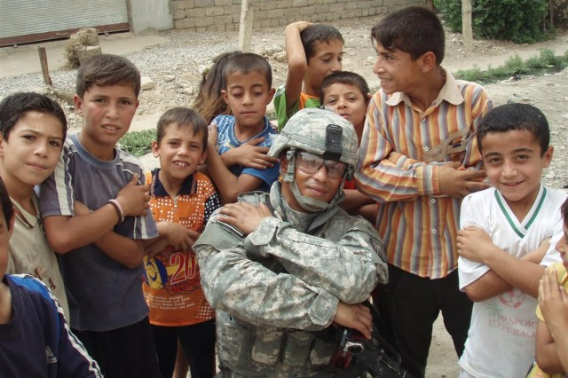 "Sgt. Guillermo Martinez Quintana, a native of Mayaguez, P.R., poses with some Iraqi children during a recent goodwill mission to a village nearby Contingency Operating Site Marez-East, Iraq. As a leader you will need to be confident on your abilities to lead our future generation of Soldiers that more than ever seek guidance from their leaders,"" he said, a redeployment movement noncommissioned officer, Headquarters and Headquarters Company, 18th Combat Sustainment Support Battalion, 16th Sustainment Brigade. When the road seems tough and the task to overwhelming, look to your left and remember that every Soldier in your section is depending on you to lead them."