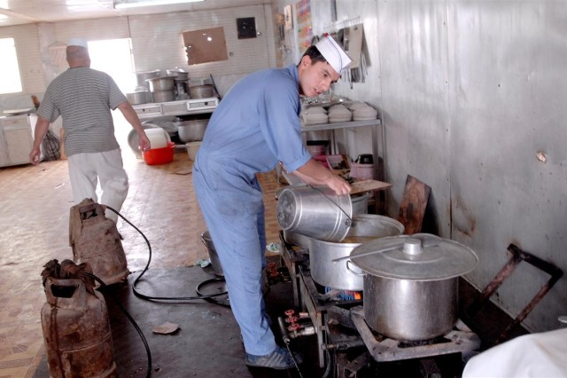 An Iraqi prepares food in the Iraqi Army Officers dining facility during a visit from the 287th Sustainment Brigade food service team at Camp Ur, Iraq June 20. The visit allowed the 287th Sust. Bde. to observe the Iraqis dining facility procedures and make quality control recommendations