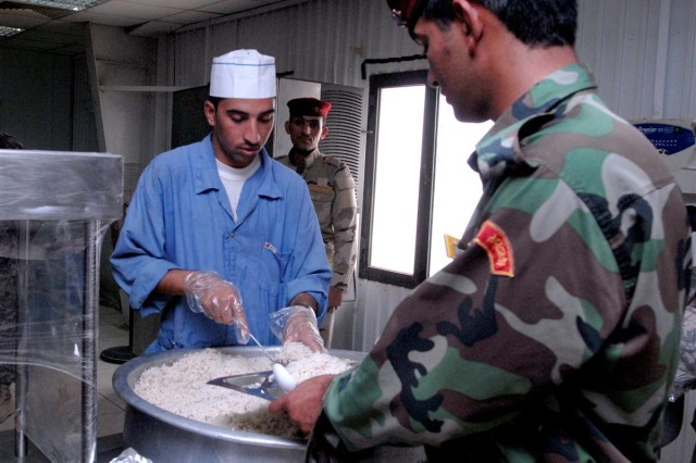 An Iraqi serves an Iraqi Soldiers at the Iraqi Army Enlisted dining facility during a visit from the 287th Sustainment Brigade food service team at Camp Ur, Iraq June 20