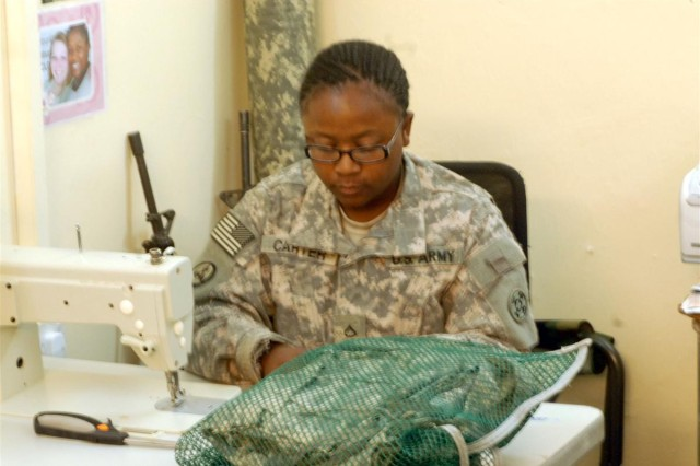 Pfc. Alysa Carter, a member of the Taji Renovation Shop and Columbus, Ohio native, reads instructions to the Army Combat Uniforms before making alterations at Camp Taji, Iraq. Carter is deployed with the 855th Quartermaster Company, 398th Combat Sustainment Support Battalion, 10th Sustainment Brigade.