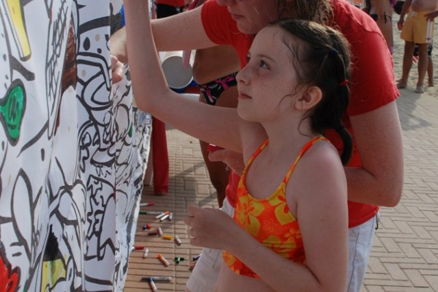 Visitors to the American Beach in Tirrenia have fun coloring on a large wall mural during the Independence Day celebration.