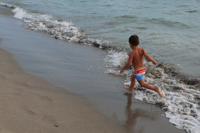 A child in his red, white and blue swimsuit tries to out run the Mediterranean waves during July Fourth celebrations in Tirrenia, Italy.