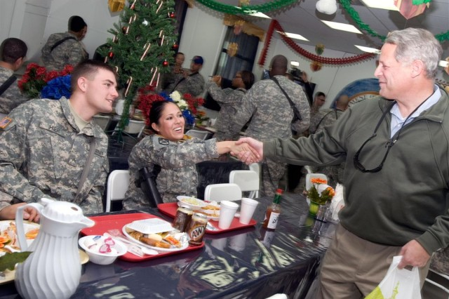 New York Congressman Steve Israel shakes hands with Sgt. Laura M. Hier, a material management NCO, 548th Combat Sustainment Support Battalion, during a holiday luncheon at Al Asad Air Base, Iraq Dec. 21. Seated to her right is her husband, Cpl. Arthur H. Hier; the couple deployed together from Fort Drum, N.Y