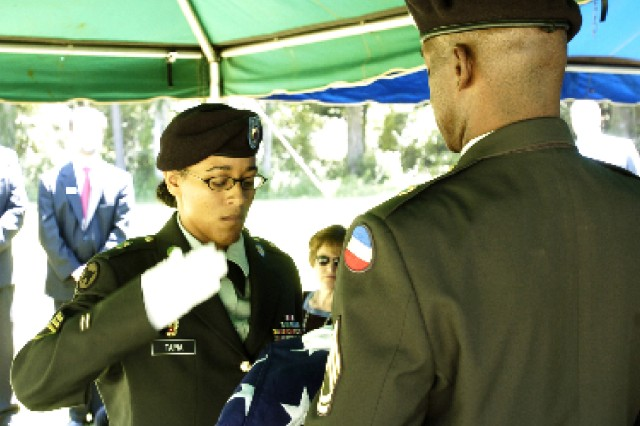 Staff Sgt. Kimberly Tapia, U.S. Army Garrison Funeral Honors team, renders the final salute to the colors, and Korean War Veteran Gerald Gendell, moments after placing three spent shell casings from a 21-gun salute inside of the folded flag during Gendell's funeral ceremony July 3. The Funeral Honors team represents Fort McPherson and the Army in rendering final honors for sevicemembers.