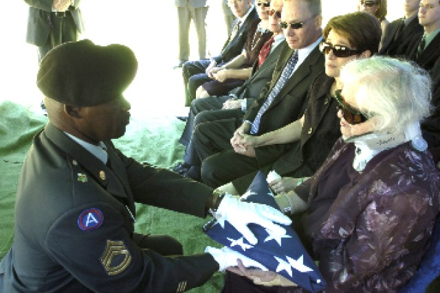 "Sgt. 1st Class Eric Houston, Funeral Honors noncommissioned officer in charge, hands the national colors to Marion Gendell, widow of Korean War Veteran Gerald Gendell, July 3. ""This was so important,"" Marion said of the honors rendered by the team at her late husband's funeral, adding that it helped the grieving process."