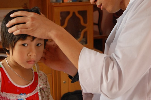 Dr. (Capt.) Charles Nguyen, a pediatrician from Tripler Army Medical Center, examines a child during the first medical readiness exercise conducted in the Bac Ninh Province in Vietnam July 8.