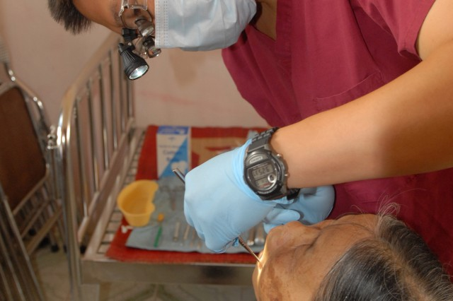 Dr. (Capt.) Michael Sun Woo, Pacific Regional Dental Command, performs a tooth extraction on a patient during the Medical Readiness Exercise held in the Bac Ninh Province of Vietnam July 8.