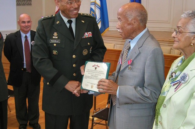 Lt. Gen. Michael D. Rochelle, the Army's G-1, presents the Bronze Star Medal to former Staff Sgt. Morris N. Bishop, for his combat service with the 92nd Infantry Division in World War II. The ceremony in Milford, Conn., took place July 6, as his wife, Rose, looked on.