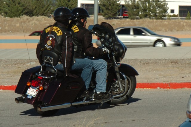 Retired Staff Sgt. Ivan Westrick takes off on his customized Harley-Davidson motorcycle with his wife Ginger, holding onto the back during a 2007 U.S. Marine Corps Toys for Tots motorcycle run in El Paso, Texas.