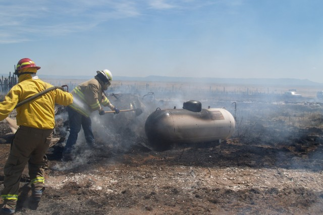 PIÑON CANYON MANEUVER SITE, Colo.- Fort Carson firefighters working out of the Piñon Canyon Maneuver Site cool off a 300-gallon propane tank at a fire near the installation July 8. The firefighters were at PCMS supporting Air Force training when they spotted the fire and assisted the local firefighters in controlling the fire and rescuing a 60-year-old man from the fire.
