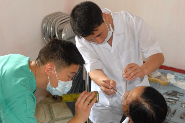 Dr. (Capt.) Michael Sun Woo, Pacific Regional Dental Command, and Dr. Duong Duc Phong, Vietnamese Army, assist each other in providing dental care during a medical readiness training exercise held in the Bac Ninh Provice of Vietnam July 10.