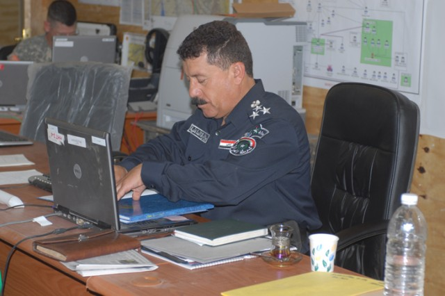 Brig. Gen. Mohammed Sala Abass, an Iraqi Police liaison officer, works at his desk inside 2nd Brigade, 1st Cavalry Division's headquarters, on Forward Operating Base Warrior, Kirkuk, Iraq, July 3. Abass, along with other liaisons, began working on FOB Warrior less than a week ago, and are helping coordinate efforts between the U.S. Military, Iraqi Police, Iraqi Army, and the Kurdish Army services.