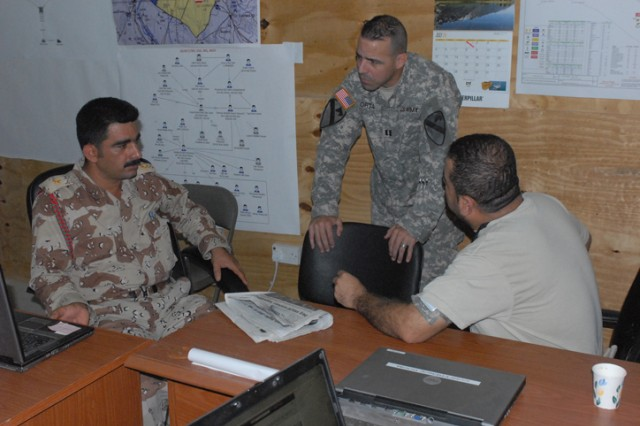 2nd Lt. Nabil Abdulla Mahmood, a Kurdish Army liaison, talks with Capt. Elmo Orta, and the Iraqi security forces logistic officer for 2nd Brigade Combat Team, 1st Cavalry Division. Mahmood is part of a group of liaisons from various Iraqi military and police organizations who are working together by sharing information and coordinating operations.