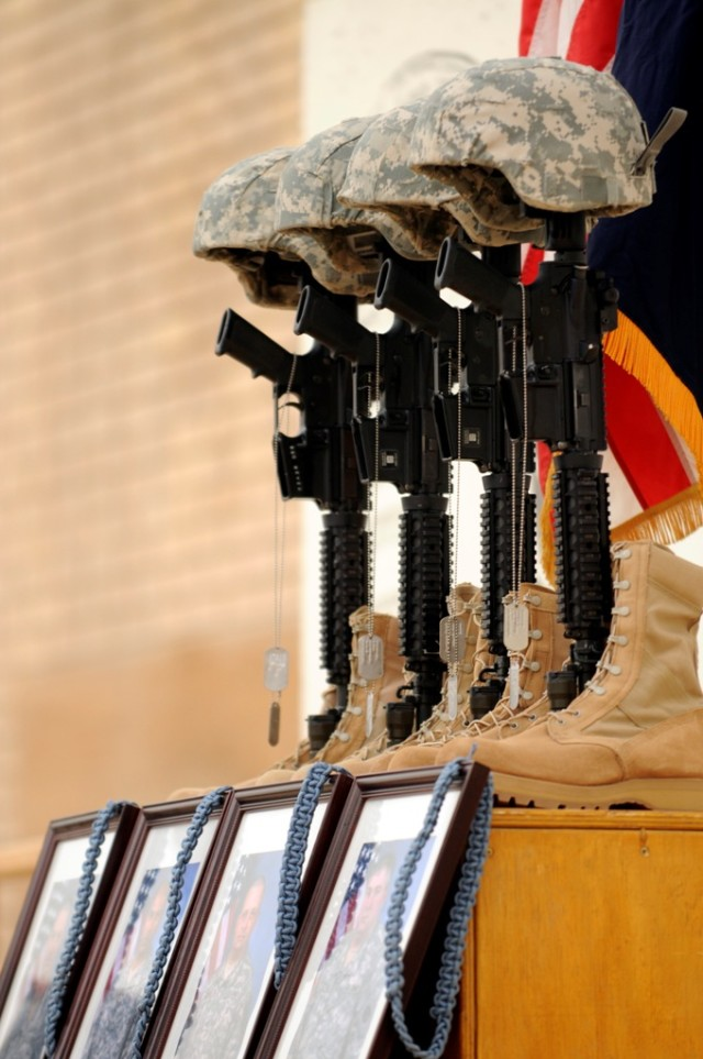 MAHMUDIYAH, Iraq - The traditional memorial of boots, rifle, helmet, and dog tags stands in honor of Sgt. First Class Edward Kramer, Sgt. Juan Baldeosingh, Sgt. Roger Adams Jr. and Spc. Robert Bittiker, during a memorial service held in their honor a...