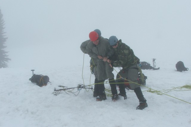 Soldiers from 1st Special Forces Group (Airborne) set up a rescue anchor system in conditions of limited visibility during medical training on Mt. Rainier. Mount Rainier, located near Ashford, Wash., is the tallest mountain in the Cascade Mountain range. The system allows Soldiers to safely retrieve a member who may fall into a crevasse or lose footing in some other manner while conducting mountaineering operations.