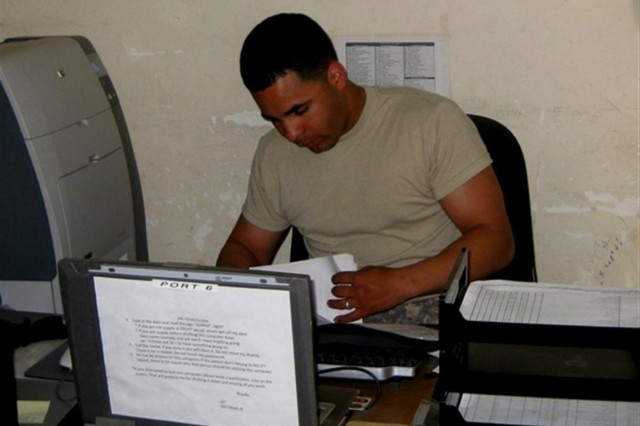 Spc. Andres Oliver, a supply specialist with the 96th Transportation Company from Fort Hood, Texas, works in his office at Camp Taji, Iraq and celebrated his Father's day deployed in support of Operation Iraqi Freedom.