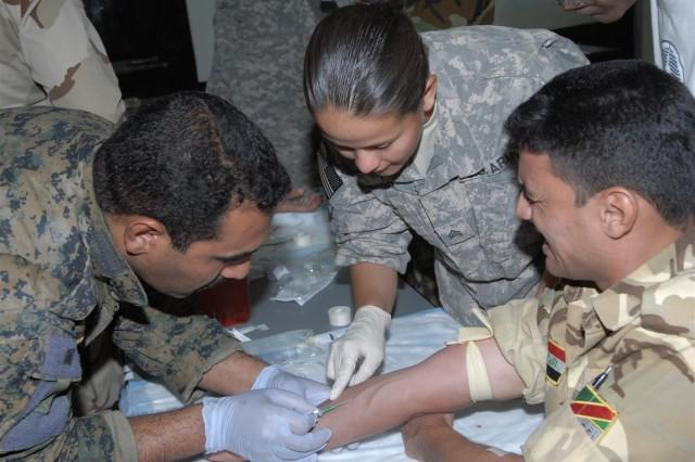 Sgt. Fedra A. Toy, a medic with Headquarters and Headquarters Company 4/1 Armored Division, and resident of El Paso, Texas, instructs Iraqi Soldiers on how to properly administer an intravenous injection during a five-day Combat Life Saver course at Contingency Operating Base Adder, Iraq June 17